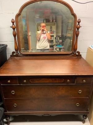A vintage dresser with mirror.