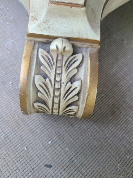 A carved foot of a pedestal dining table.