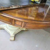 A wooden dining table with a white colored base.