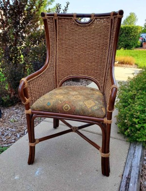 A vintage chair with a woven seat back.