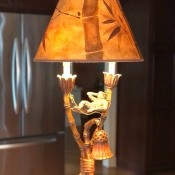 A lamp that has a monkey under the shade.