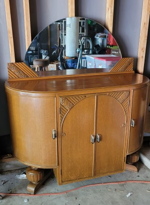 A small buffet table with a mirror.