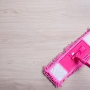 A pink dust mop on a hardwood floor.