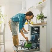 A woman unloading a dishwasher.