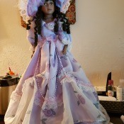 A porcelain doll with dark hair and a fancy lavender outfit.