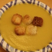 A bowl of zucchini soup with croutons.