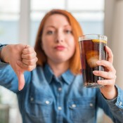 A disapproving woman with a glass of soda