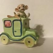 A monkey in a old fashioned car.