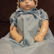 A baby doll in a bonnet and blue dress.