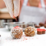 Adding sprinkles to chocolate candy.