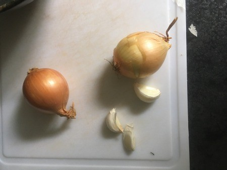 Onions and garlic on a cutting board.