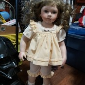 A young girl porcelain doll with light brown hair.