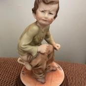 A figurine of a boy on a chamberpot.