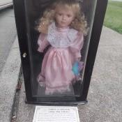 A porcelain doll in a decorative box.