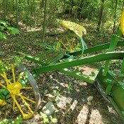 An old fashioned green and yellow grader.
