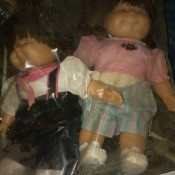 Two Cabbage Patch dolls in a bag.