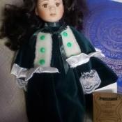 A doll wearing a green velvet dress.