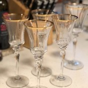 A collection of gold rimmed champagne flutes.