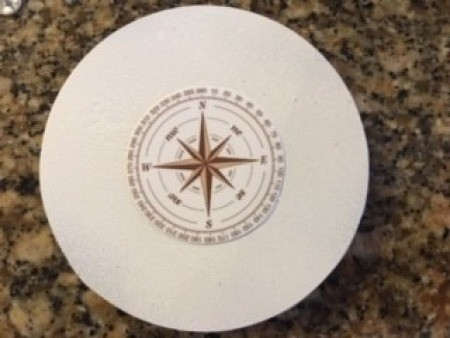 A compass rose on a white circular piece of paper.