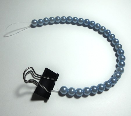 Using a binder clip to hold the beads on a string.
