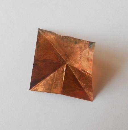 Folding the copper into a triangle.