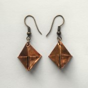 Two earrings made from copper foil.