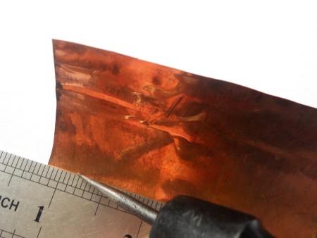 Cutting a square of copper foil.