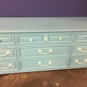 A wooden dresser painted blue.