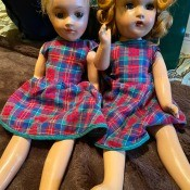 Two old dolls wearing matching dresses.