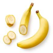 A whole banana and a cut banana on a white surface.