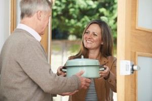 A man giving a pot to a woman at the door.