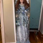 A porcelain doll next to it's box.