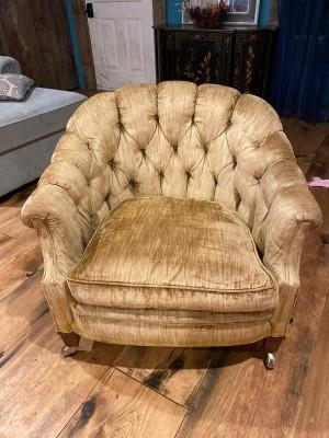 An armchair upholstered in tan velvet.