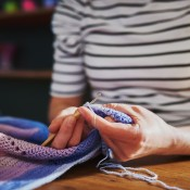 A woman sewing an edge on a blanket.