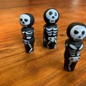 Three skeleton peg dolls.